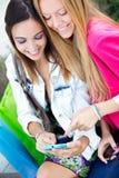 Zwei Freunde, die Spaß mit Smartphones haben Stockbilder