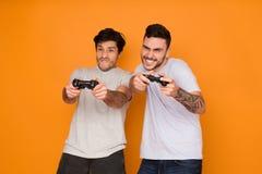 Zwei Freunde, die Videospiele über orange Hintergrund spielen stockfoto