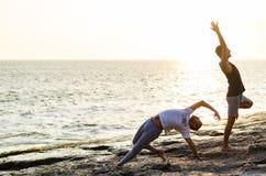 Zwei Freunde, die Yoga am Rand des Ozeans bei Sonnenuntergang üben stockfotos