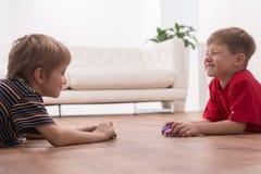 Zwei Freunde, die zu Hause auf Boden spielen Stockfotografie