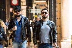Zwei Freunde gehen durch die Straßen in einem beschäftigten Bereich lizenzfreie stockfotografie
