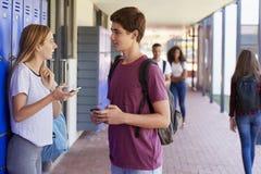 Zwei Freunde mit Smartphones sprechend im Schulkorridor Stockfotografie