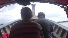 Zwei Freunde reisen auf das sich schnell bewegende touristische hölzerne Boot mit Koffer im wolkigen Wetter in Nationalpark Khao  stock video footage