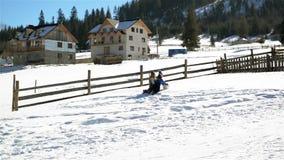 Zwei Freunde rollen enormen Schneeball herauf den Hügel und das dritte Mädchen läuft, um ihnen zu helfen Glückliche Kinder spiele stock footage