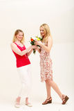 Zwei Freunde tauschen ein Blumengeschenk aus Stockbilder