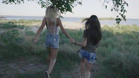 Zwei Freundfrauen, die entlang Straße am Reisen laufen Blondine und Brunette, die im Urlaub Spaß lächeln und haben steadicam stock video