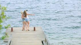 Zwei Freundfrauen, die selfie mit Handy nahe dem Fluss nehmen Zwei junge Mädchen, die nahe Fluss genießen und Selfie nehmen stock video