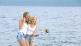Zwei Freundfrauen, die selfie mit Handy nahe dem Fluss nehmen Zwei junge Mädchen, die nahe Fluss genießen und Selfie nehmen stock footage