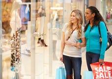 Zwei Freundin-Fenster-Einkaufen mit Taschen Stockfotos