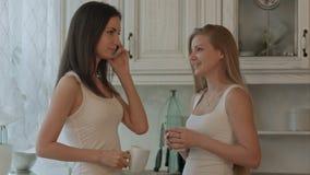 Zwei Freundin mit trinkendem Kaffee des Telefons oder stock footage