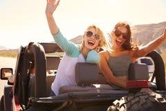Zwei Freundinnen auf Autoreise auf der Rückseite des konvertierbaren Autos stockfotografie