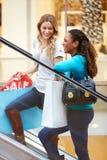 Zwei Freundinnen auf Rolltreppe im Einkaufszentrum Stockbilder