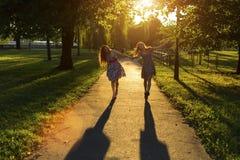 Zwei Freundinnen der jungen Mädchen gehen zusammen entlang den Park in den Hintergrundbeleuchtungsstrahlen der untergehenden Sonn Lizenzfreie Stockfotografie