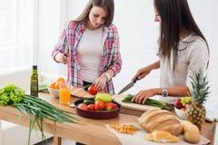 Zwei Freundinnen, die Abendessen in einer Küche vorbereiten stockbild