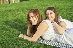Zwei Freundinnen, die auf dem Rasen liegen stockbilder