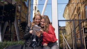 Zwei Freundinnen, die digitale Tablette im Freien verwenden Lächelnde Freundinnen, die über Fotos auf dem Tablettengerät, gehend  stock video