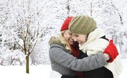 Zwei Freundinnen, die draußen im Winter umarmen Stockbild