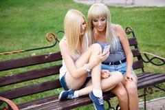 Zwei Freundinnen, die ein smartphone verwenden lizenzfreies stockbild