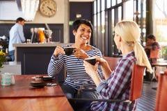 Zwei Freundinnen, die an einer Kaffeestube sprechen stockbild