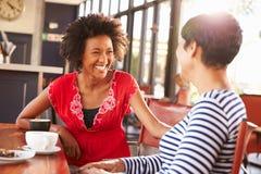 Zwei Freundinnen, die an einer Kaffeestube sprechen lizenzfreie stockbilder