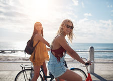 Zwei Freundinnen, die ihr Fahrrad entlang Küstenpromenade fahren Stockbild