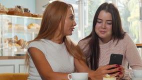 Zwei Freundinnen, die Internet durch intelligentes Telefon an der Kaffeestube surfen stock video footage