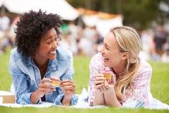 Zwei Freundinnen, die kleine Kuchen Sommer-Ereignis am im Freien genießen Lizenzfreies Stockfoto