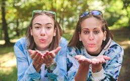 Zwei Freundinnen, die Kuss zur Kamera durchbrennen Stockfotos
