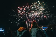 Zwei Freundinnen, die schöne helle bunte Feuerwerke im nächtlichen Himmel genießen lizenzfreie stockfotografie