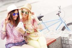 Zwei Freundinnen, die Smartphone beim Fahren Tandemfahrrads verwenden lizenzfreies stockfoto