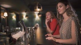 Zwei Freundinnen, die am wartenden Barzähler sitzen, wenn Barmixer sie Cocktails macht Freizeit von schönen Mädchen stock video