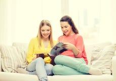 Zwei Freundinnen, die zu Hause Zeitschrift lesen Lizenzfreie Stockfotografie