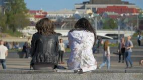 Zwei Freundinnen entspannen sich in der Stadt und passen Sportspiele - slowmo 180 fps auf stock video