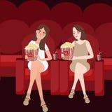 Zwei Freundinnen genießen, Filme am Kino beim Essen von Popcornfreundschaft aufzupassen Stockfoto