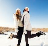 Zwei Freundinnen haben Spaß und genießen frischen Schnee Stockfotografie