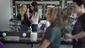 Zwei Freundinnen im Kosmetiksalon Mädchen bereiten sich für eine Partei vor Der Maskenbildner tut ein Make-up die blonde Frau an stock footage