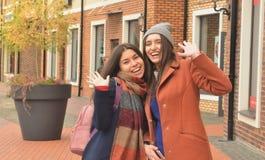 Zwei Freundinnen Lächeln im Freien und Wellenartig bewegen an der Kamera Stockbild