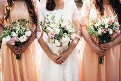 Zwei Freundinnen und eine Braut halten schöne Hochzeitsblumensträuße in t Stockfotos