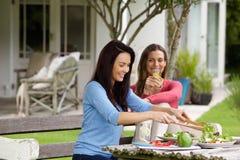 Zwei Freundinnen, welche die Außenseite zu Mittag isst sitzen Lizenzfreies Stockfoto