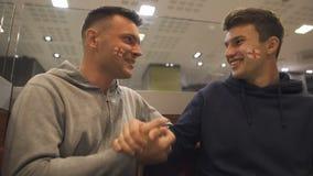 Zwei freundliche Fußballfane treffen unerwartet sich vor Match, männliche Freizeitbetätigung stock video
