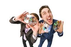 Zwei freundliche Geschäftsmänner, die DVDs auf Verkauf anbieten Lizenzfreies Stockfoto