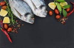 Zwei frische dorado Fische auf schwarzem Schieferschneidebrett Lizenzfreie Stockbilder