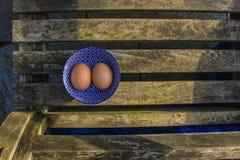 Zwei frische Eier in der schönen blauen Schüssel mit Muster Lizenzfreie Stockfotografie