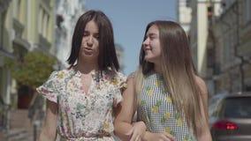 Zwei frohe Frauen mit Einkaufstaschen gehend durch Stadtstraße Junge Mädchen, die das stilvolle Sommerkleidergenießen tragen stock video