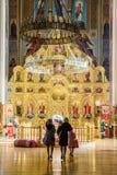 Zwei fromme Frauen mit ihren Kindern sind zu St. Ekaterina Orthodox Cathedral gekommen zu beten und anzubeten Vertikale Innenansi Stockbild