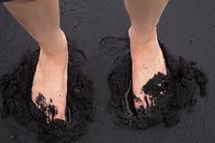 Zwei Fuß, der in den schwarzen Sand sinkt Stockfotografie