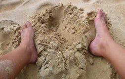 Zwei Fuß um Loch im Strandsand Stockfotos