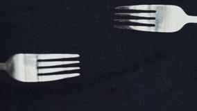 Zwei Gabeln greifen sich auf einem schwarzen Hintergrund an Die Bewegung der Gabeln stock footage