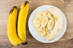 Zwei ganze gelbe Bananen und Scheiben von Bananen in der Platte Stockfoto