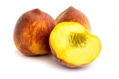 Zwei ganze Pfirsiche und ein geschnittener Pfirsich lokalisiert auf weißem Hintergrund lizenzfreie stockfotografie